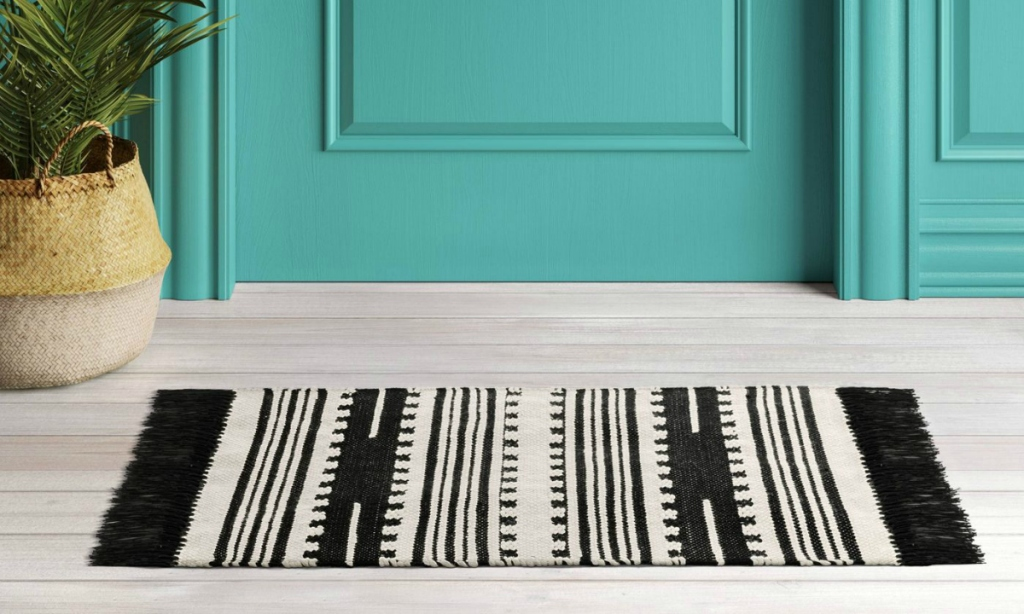 black rug in front of teal door