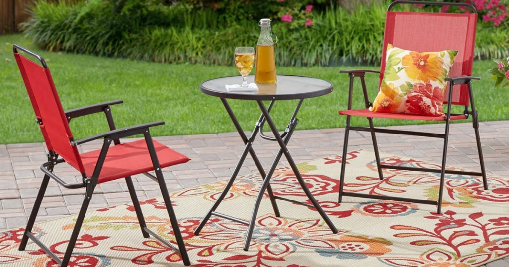 3-piece bistro set in red on outdoor rug in backyard