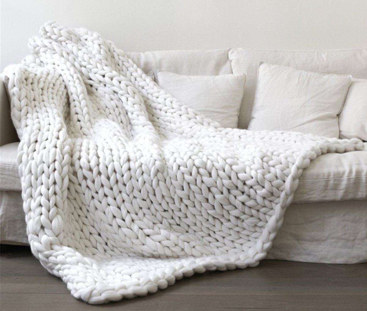 white chunky knite throw blanket on white couch